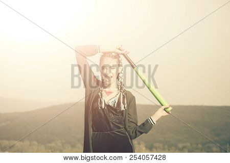 Sport or criminal girl outdoor. Hooligan on blue sky. Bandit gang and conflict. Beauty and fashion. Woman smiling with baseball bat. poster