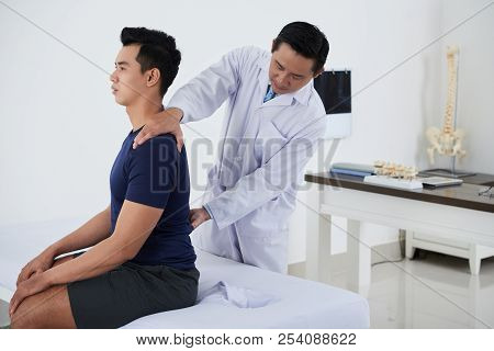 Osteopath Checking Spine Of Sitting Young Vietnamese Man