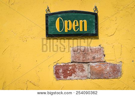 Open Sign On A Yellow Grunge Brick Wall With A Green Sign