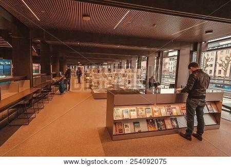Ghent, Belgium - Mar 30, 2018: Reader Watching Bookshelf With New Books Inside The Public Library De