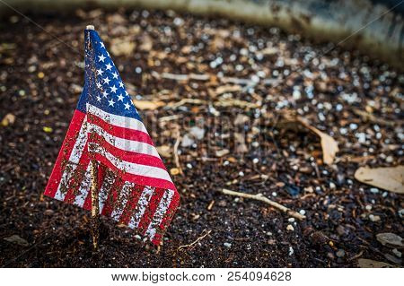 A Miniature Us Flag Sits In A Flower Planter Partially Covered With Dirt..