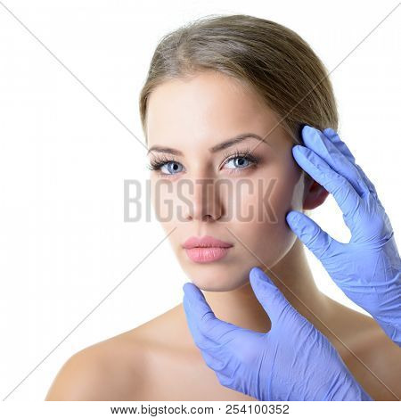 Beauty treatment for young beautiful female face, doctor's hand in gloves touch face of beautiful young woman . Skin care, beautician treatments, body wax, mink eyelashe, eyebrow grooming