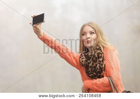 Lovely Fashion Woman In Fall Autumn Park Taking Selfie Self Photo Picture. Pretty Cute Young Girl In