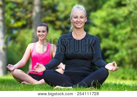 Mature fit healthy middle aged female yoga teacher yogi teaching young woman at yoga practice outside in a natural tranquil green environment