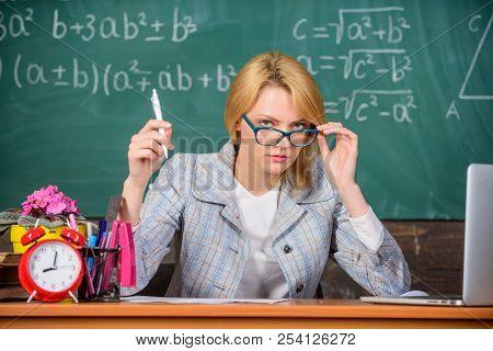 Teacher Woman Sit Table Classroom Chalkboard Background. Teacher Suspiciously Peeking Out Of Eyeglas