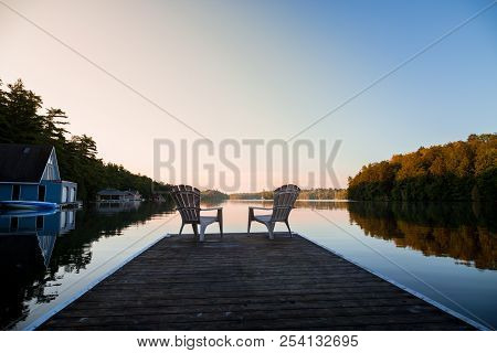 Muskoka Chairs Sitting At The End Of A Dock In Front Of Lake Joseph At Sunrise.