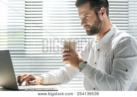 Concentrated Businessman Holding Disposable Cup Of Coffee And Working With Laptop Near Window With J