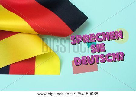 some flags of Germany and the question sprechen sie deutsch? do you speak German? written in German, on a green background