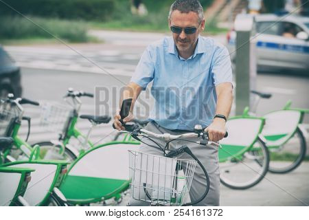 Man riding a bike in his way to work, concept of using city bike as environment friendly way of getting to work
