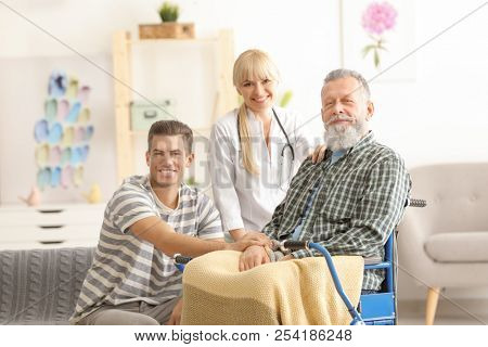 Caregiver with senior man and his son at home