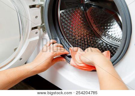 Photo of female hands wiping washing machine with open doorindoors
