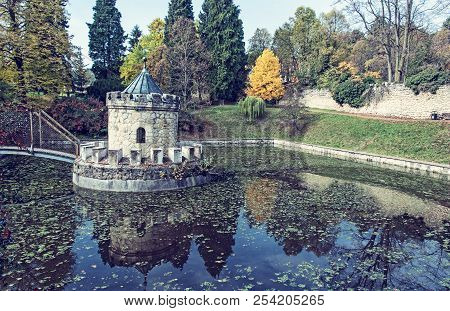 Turret in Bojnice, autumn park, lake and colorful trees. Slovak republic. Seasonal natural scene with beautiful pond. Blue photo filter. poster