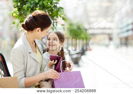 Adorable little girl sitting with mother on bench in shopping mall and opening bags with purchases looking happy