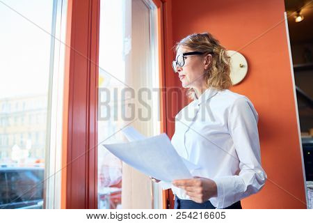 Elegant pensive woman in glasses holding papers and looking away in window contemplating on work