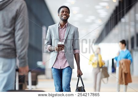 Cheerful African-American man standing with passport in hall of airport