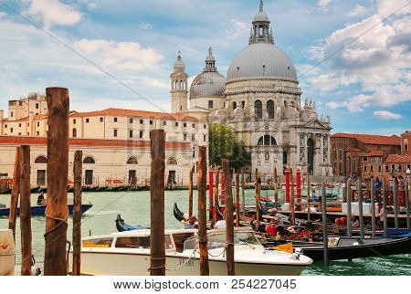 Venice, Italy, Jun 8, 2018: Moored Gondolas With Basilica Di Santa Maria Della Salute In The Backgro