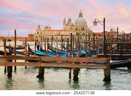 Venice, Italy, Jun 8, 2018: Gondoliers With Tourists Riding Gondolas Across Grand Canal With Basilic