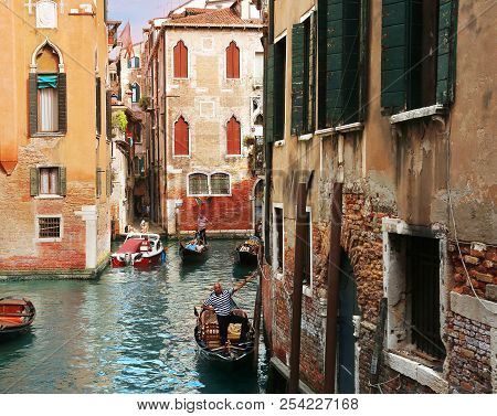 Venice, Italy, Jun 8 2018: Classic Venetian View With Gondoliers On Gondolas With Tourists In A Smal