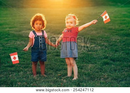 Happy Adorable Little Blond Caucasian And Hispanic Latin Girsl Smiling Holding Hands And Waving Cana