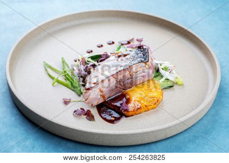 Modern style Japanese bonito tuna fish filet with vegetable and pineapple glazed in teriyaki sauce as closeup on a plate poster