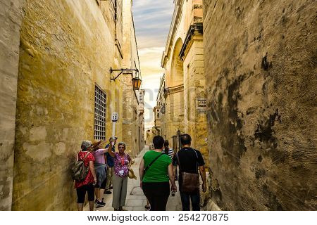 Mdina, Malta - September 14 2017: A Tour Guide Waits For Her Tour Group To Catch Up During A Walking