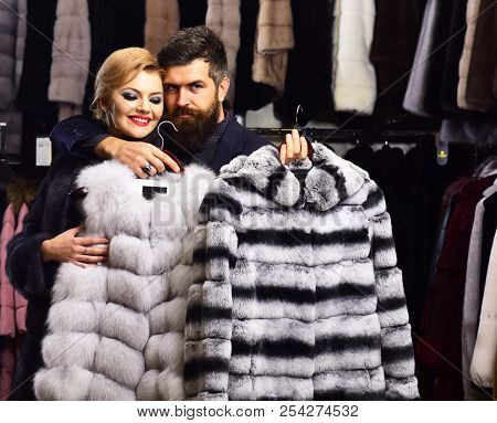 Man With Strict Face And Woman With Coats In Fur Shop. Woman With Smiling Face In Black Fur Coat Wit