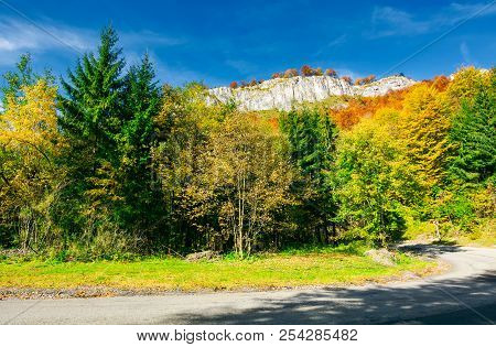 Road Though Forest In To The Mountain. Rocky Cliff Hang Over The Way. Lovely Autumn Scenery