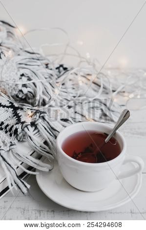 Cup Of Red Hibiscus Tea, Book, Lights For Home Decoration And Woolen Knitted Blanket On Wooden Table