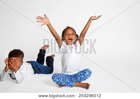 A Set Of Siblings, Boy And Girl African American Kids.  The Girl Is Center Stage, Arms In The Air, M