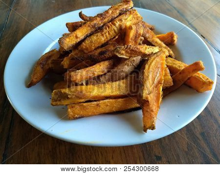 A Plate Of Home-made Rough Cut Sweet Potato Fries On A Table