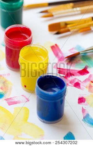 Tempera paint of different colors green blue yellow red brushes on white paper background with colorful strokes. Arts painting creativity education hobbies concept. Lifestyle