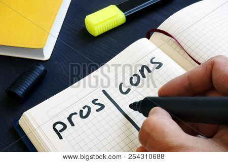 Man Is Writing List Of Pros And Cons.