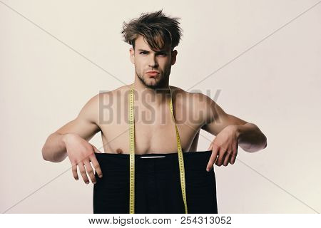 Athlete With Messy Hair And Naked Torso. Man Holds Black Jeans Of Large Size And Yellow Measuring Ta