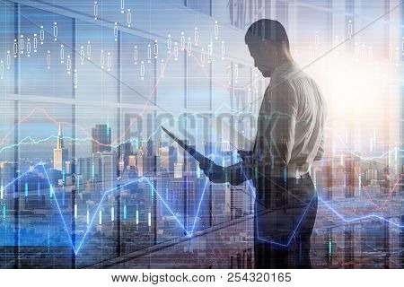 Side View Of Attractive Young European Man On City Background With Forex Chart. Finance And Trade Co