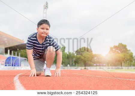 Fit And Confident Fat Boy In Starting Position Ready For Running. Kid Athlete About To Start A Sprin