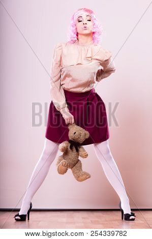 Mental disorder concept. Young childlike woman wearing like puppet doll holding teddy bear toy studio shot poster