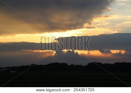 Dark Clouds With Several Sunbeams During Sunset In Colorful Sky In The Netherlands.