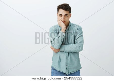 Portrait Of Bored Pissed Attractive Male Student In Shirt, Leaning Face On Head And Staring At Camer