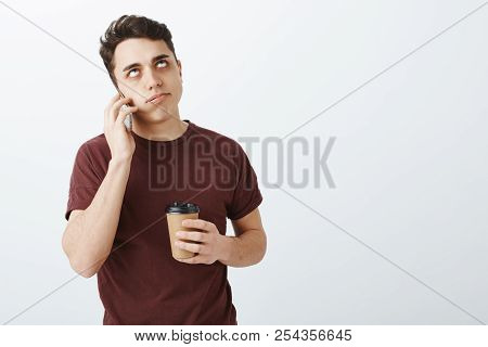 Annoyed Bothered Handsome Man With Short Dark Hair, Holding Cup Of Coffee And Smartphone Near Ear, R