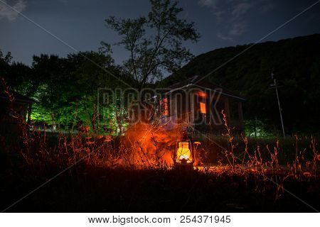Horror Halloween concept. Burning old oil lamp in forest at night. Night scenery of a nightmare scene. Selective focus. poster