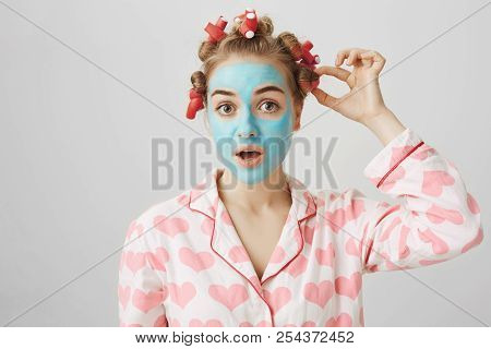 Funny White Female In Hair-curlers And Pyjamas With Heart Print, Standing In Face Mask And Looking A
