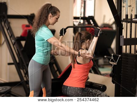 Fitness trainer assisting young woman with excercise in gym