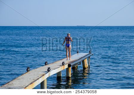 A Beautiful Girl In A Blue Bikini Walks The Pier To The Sea. Marine Concrete Pier. Jumping Into The