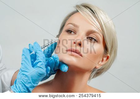 Woman Is Getting Filler Injection In Cheeks. Anti-aging Treatment And Face Lift. Cosmetic Treatment.