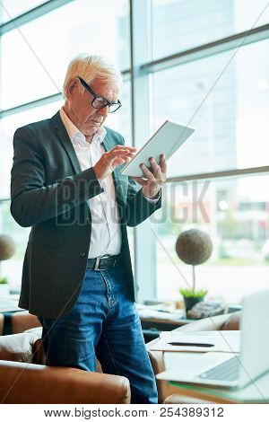 Side View Portrait Of Successful Senior Businessman Using Digital Tablet And Browsing Internet While