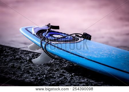 New Surfboard On The Coastline At Sunrise On The Ocean. Blue Surf Board Laying On The Coastline Wait