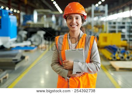 Waist Up Portrait Of Cheerful Young Woman Wearing Hardhat Smiling Happily Looking At Camera While En