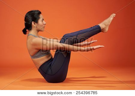 Yoga Half Boat Asana Pose. Woman In Half Boat Asana Yoga Pose On Studio Background