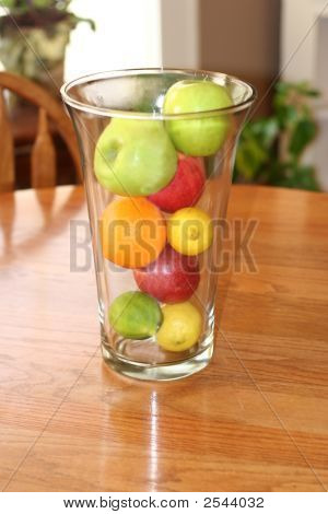 Clear Vase With Fresh Fruit On Wooden Dining Table