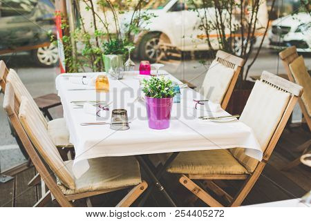 Cafe Terrace In Small European City. Beautiful Terrace Or Balcony With Small Table, Chair And Flower